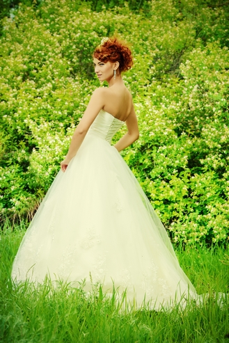Lovely elegant red-haired bride stands on the lawn. Wedding dres
